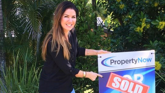 a woman pointing to a PropertyNow for sale sign with the word 'SOLD' added to it