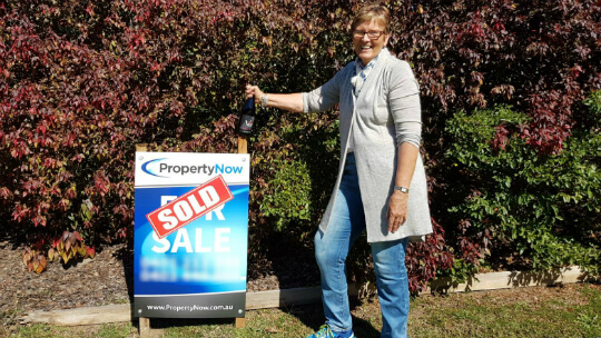 a woman smiling beside a PropertyNow for sale sign with the word 'SOLD' added to it