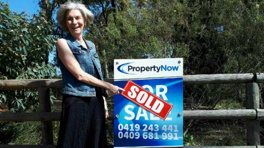 a woman happily pointing to a PropertyNow for sale sign with the word 'SOLD' added to it