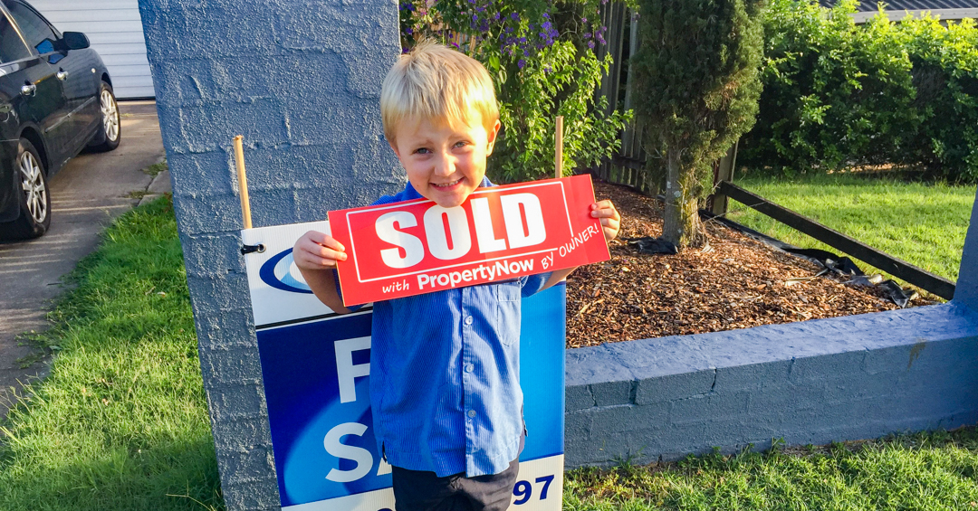 a little boy holding a SOLD sign