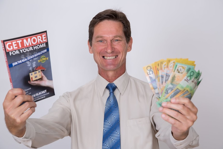 Andrew Blachut holding a copy of his Get More For Your Home book in one hand and paper bills in the other