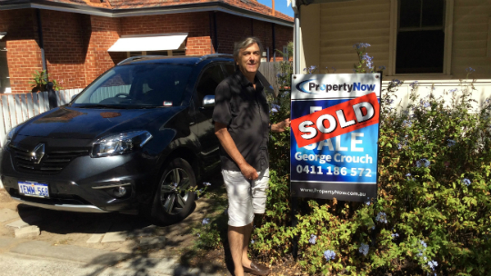 a black car and a man standing next to a PropertyNow for sale sign with the word 'SOLD' added to it