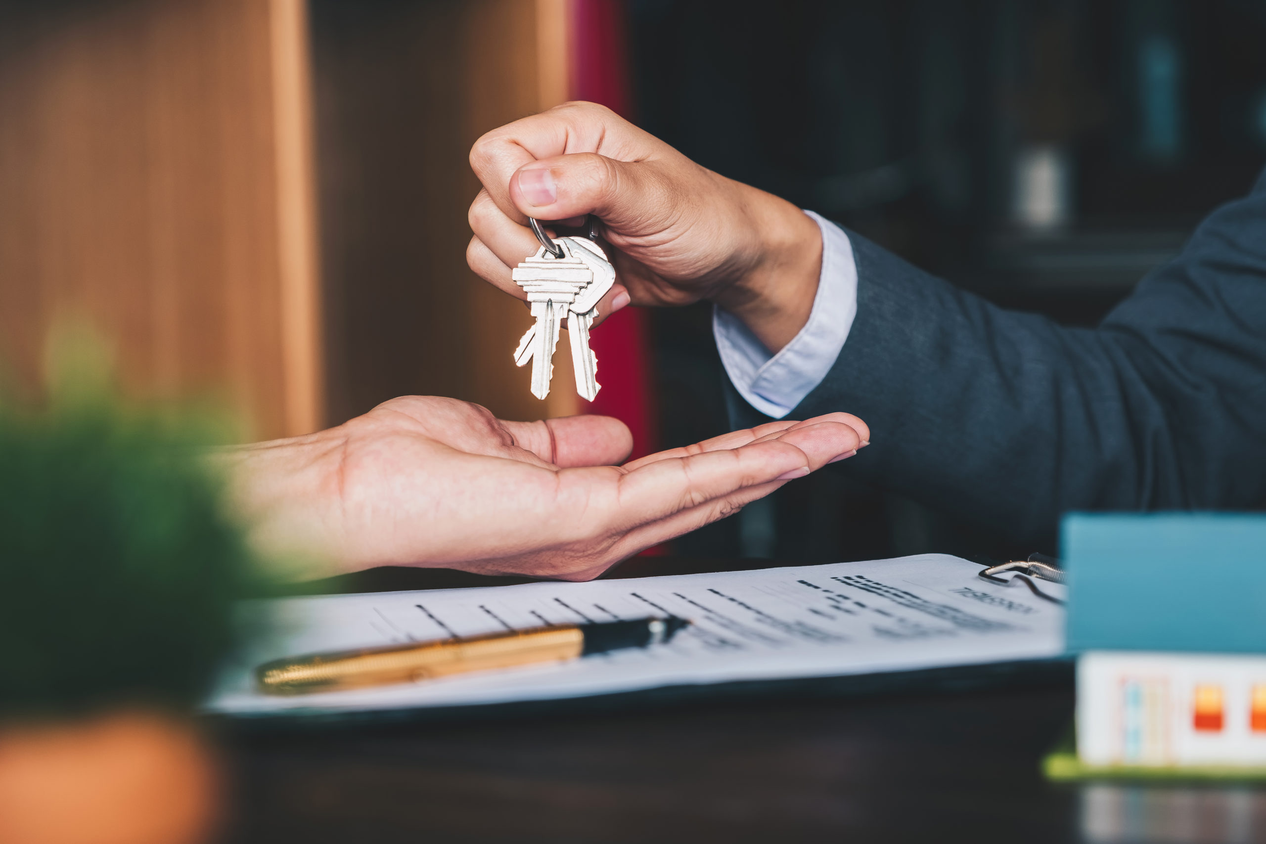 a hand giving a set of keys to another hand and a contract on the table
