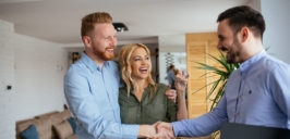a man and a woman happily getting the keys from an agent