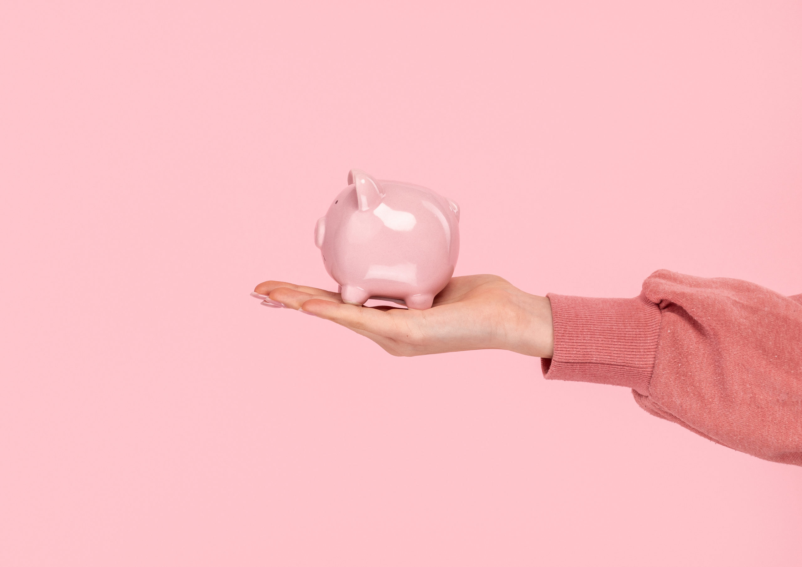 a hand holding a pink ceramic pig