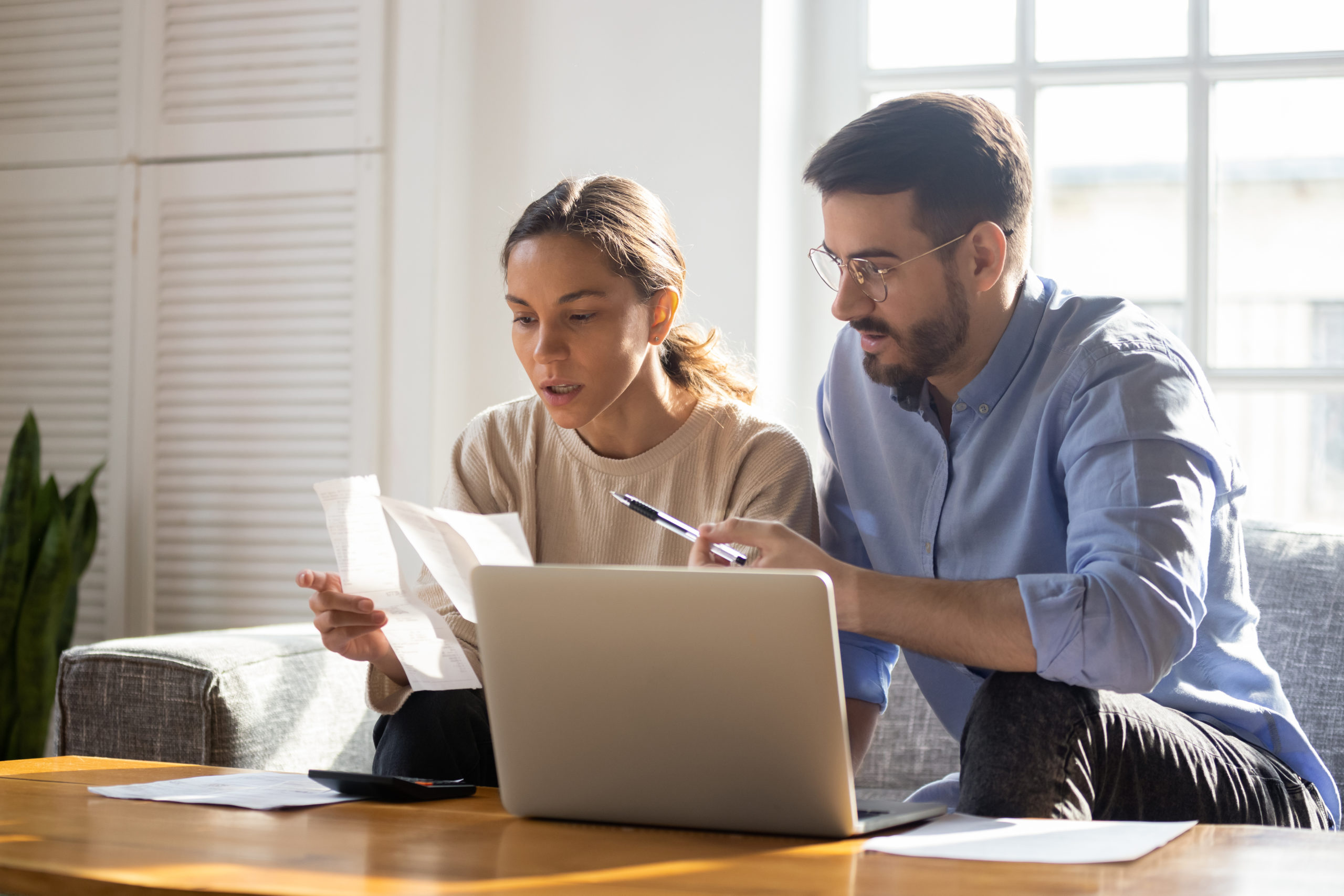a woman and a man infront of a laptop while looking at pieces of paper