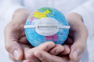 a man's hands holding a small globe with the word 'coronavirus' on it
