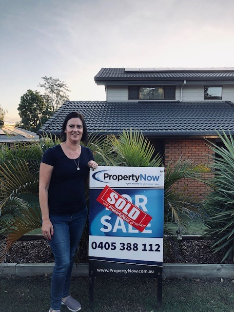 a woman standing next to a PropertyNow for sale sign with a sticker that says 'SOLD' on it