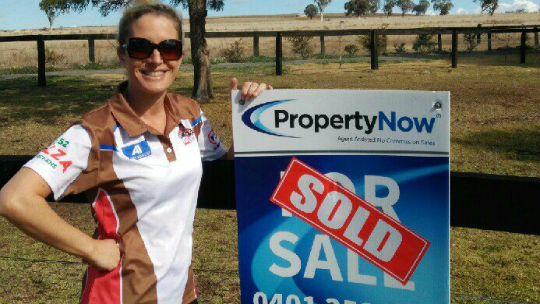 a woman wearing shades while standing next to a PropertyNow for sale sign with the word 'SOLD' added to it