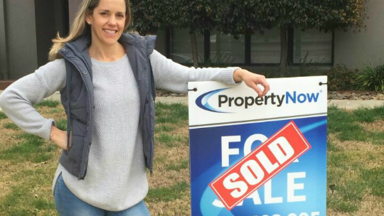 a woman wearing a grey vest standing next to a PropertyNow for sale sign with the word 'SOLD' added to it