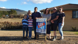 a family of 7 standing next to a PropertyNow for sale sign with a sticker that says 'SOLD' on it