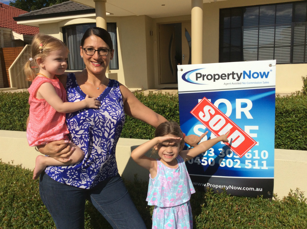 a woman and her two little girls standing next to a PropertyNow for sale sign with the word 'SOLD' added to it