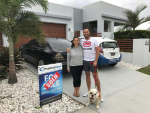 a woman and a man with their dog standing next to a PropertyNow for sale sign with the word 'SOLD' added to it