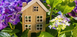 a small wooden toy house surrounded with flowers