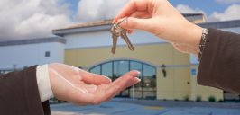 Agent Handing Over the Keys in Front of Business Offi