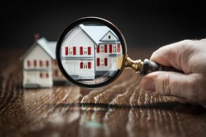 Hand Holding Magnifying Glass Up To Model Home