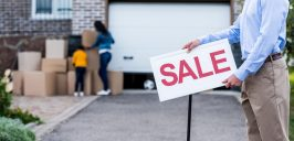Realtor with sale signboard
