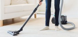 Close up of woman legs with vacuum cleaner
