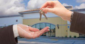 Agent Handing Over the Keys in Front of Business establishment