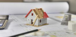 Construction plans with drawing tools and House Miniature on bluprint